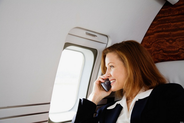 Businesswoman Using Cell Phone on Private Jet. Photo by Sam Churchill. License: CC BY 2.0.